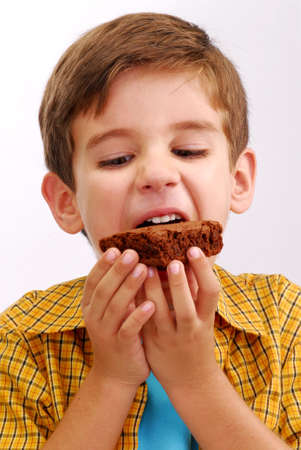 Happy little kid eating chocolate brownie Stock Photo