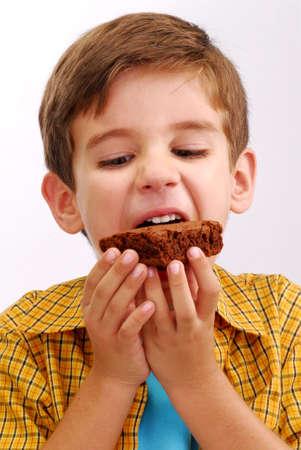 chomp: Happy little kid eating chocolate brownie Stock Photo