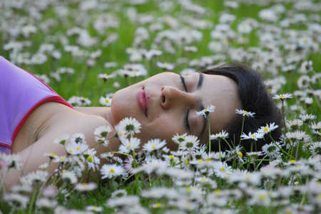 unwind: Beautiful woman lying in field of flowers Stock Photo