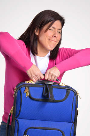 carrying: Woman carrying a heavy luggage
