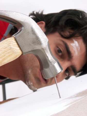 hammering: A young man is hammering a nail Stock Photo