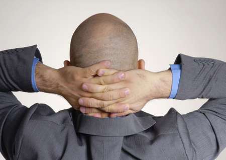 Bald businessman stretching and holding his neck  photo