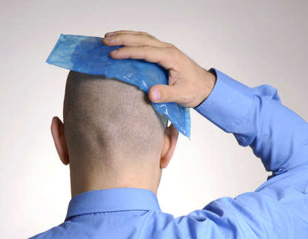 holding head: Bald man puts an ice pack over his head