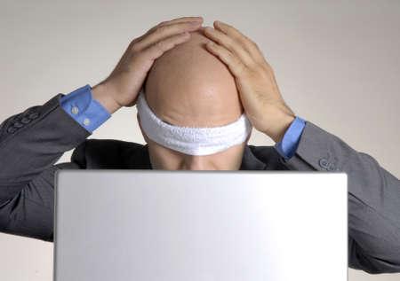 ojos vendados: hombre calvo vendaron los ojos usando una computadora Foto de archivo