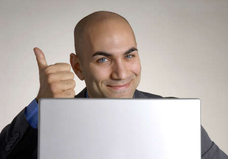 Bald businessman gives a thumbs up in front of his laptop Stock Photo - 23353843