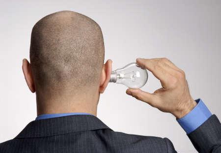 bald man: Hombre de negocios calvo que sostiene una bombilla en la oreja