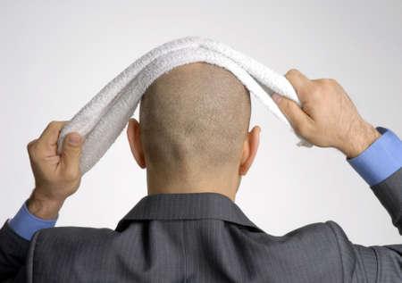 bald man: Hombre calvo sosteniendo una toalla sobre su cabeza