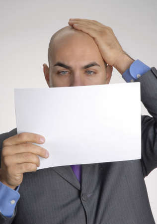 bald man: Bald man is looking at a piece of paper  Stock Photo
