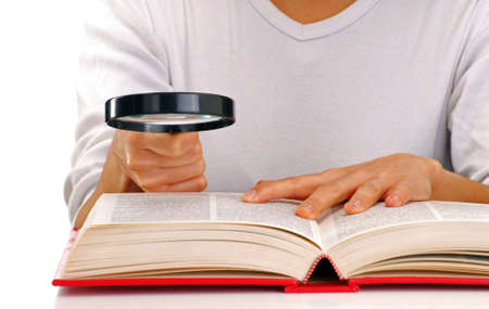 Woman holding a magnifying glass to read a book photo