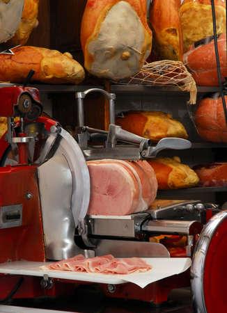 slicer: Ham slicer and prosciutto ham in a butcher shop
