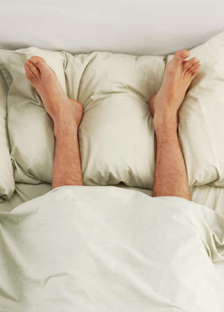 Portrait of a barefoot on bed Stock Photo