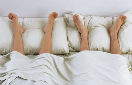 Barefoot couple lying down on bed photo