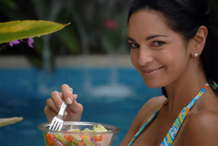 nutritive: Hispanic woman is having a bowl of salad beside the swimming pool Stock Photo