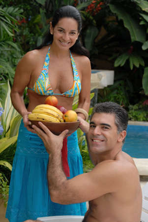 Hispanic couple is holding a fruit platter photo