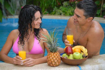 Hispanic couple spending time together in a swimming pool photo