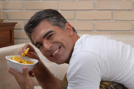 Hispanic man having sliced oranges  Stock Photo - 22388278