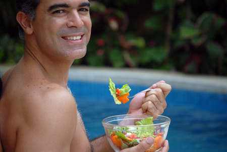 Hispanic man having a bowl of salad near the swimming pool Stock Photo - 22388280