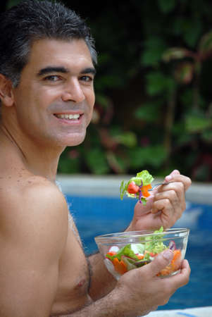 Hispanic man having a bowl of salad near the swimming pool Stock Photo - 22388282