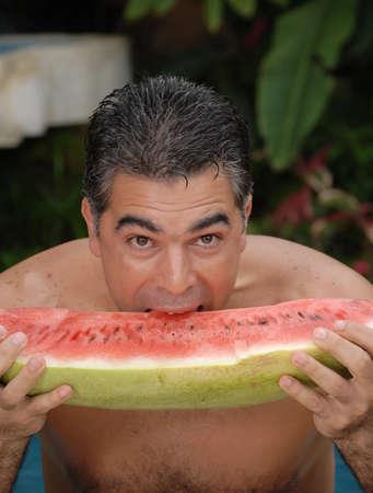 Hispanic man eating a big watermelon inside the swimming pool Stock Photo - 22388288