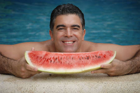Hispanic man eating a big watermelon inside the swimming pool Stock Photo - 22388289