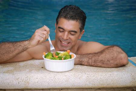 Hispanic man having a bowl of salad inside the swimming pool Stock Photo - 22388290