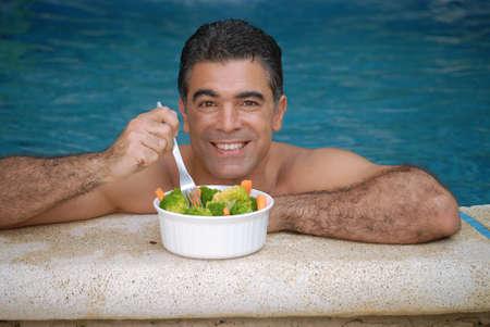 Hispanic man having a bowl of salad inside the swimming pool Stock Photo - 22388291