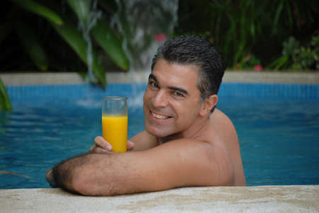 Hispanic man drinking orange juice in a swimming pool Stock Photo - 22388292