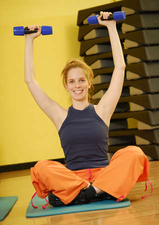 Young blonde woman doing fitness exercise with hand weights photo