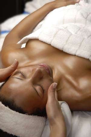 woman towel: Beautiful young black woman getting a face treatment at beauty salon
