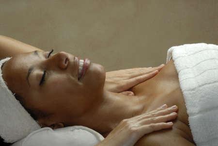 Beautiful young black woman getting a shoulder massage at beauty salon