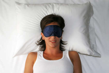 Woman lying on bed with her sleeping eye mask photo
