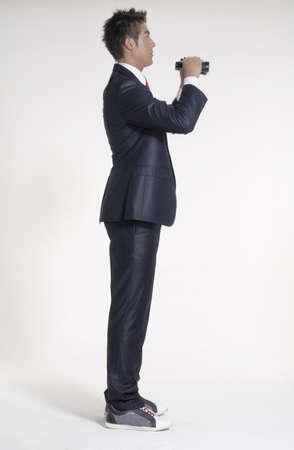 Businessman is holding the binocular on white background photo