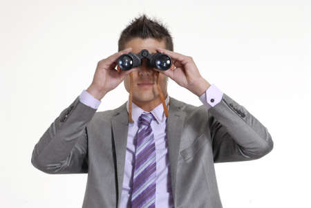 Close up of businessman looking through binoculars on white background photo
