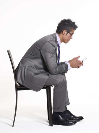 Young businessman sitting on a chair and using his handphone Stock Photo - 22290819