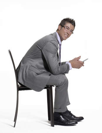 Young businessman sitting on a chair and using his handphone Stock Photo - 22290828