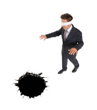 blindfold businessman approaching to a black hole