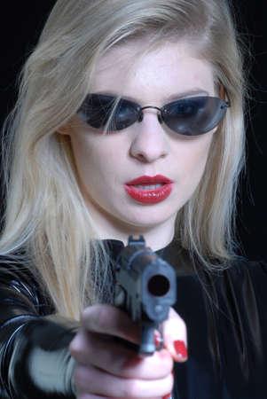 Mysterious woman pointing gun at camera photo