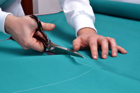 A tailor cutting fabric Standard-Bild
