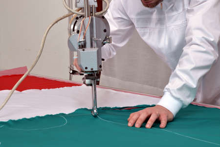 Person moving a cutting machine across cloth