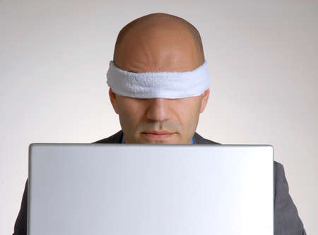 Businessman with a blindfold and laptop photo