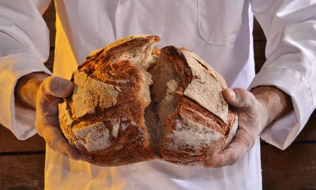 tranches de pain: Cuire tenant du pain frais. Baker tenant un pain frais sorti du four.
