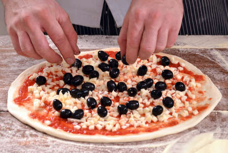provocative food: Adding ingredients on pizza.