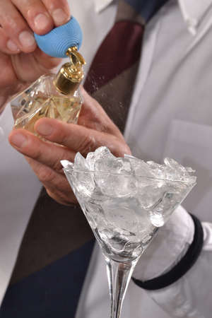 scent: Barman preparing alcoholic cocktail drink and.spraying scent on ice glass.