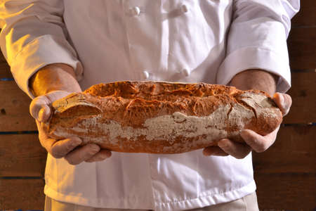 cook out: Cook holding fresh bread. Baker holding a fresh bread taken out of the oven.