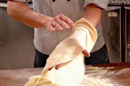dexterity: Cook preparing pizza dough.
