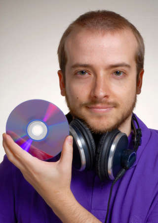 disk jockey: Young disk jockey holding a compact disc.Young man using headphones.