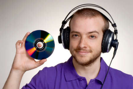 Young disk jockey holding a compact disc.Young man using headphones. photo
