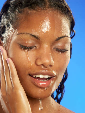 Jonge afro Amerikaanse vrouw haar gezicht wassen.