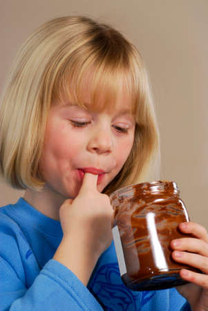 provocative food: Little girl eating chocolate cream.Kid eating nut chocolate cream. Stock Photo