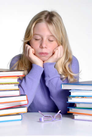 Exhausted school girl portrait behind books after studding.